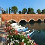 Een brug met bootjes in Peschiera del Garda